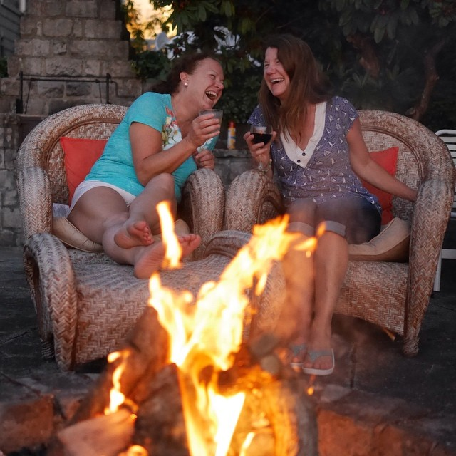 2 girls laughing by the fire